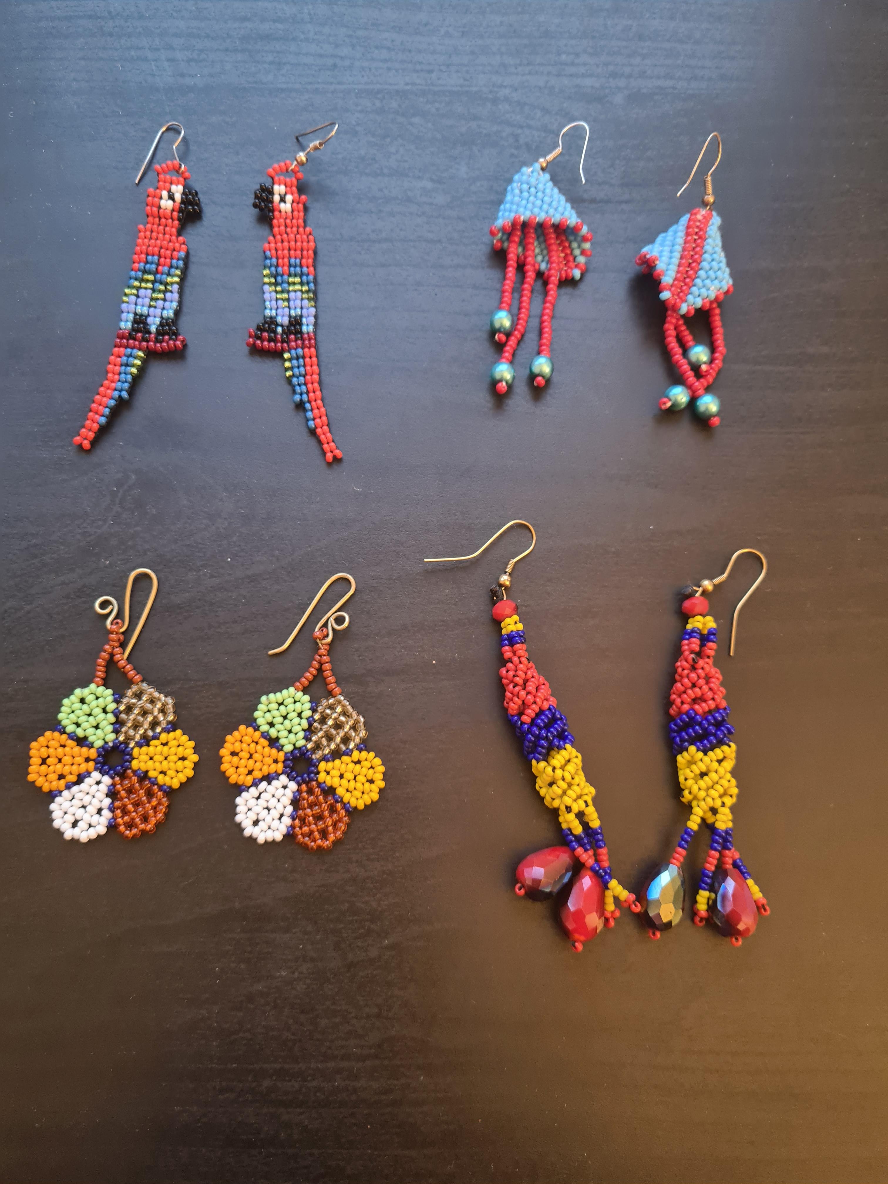 Fyra par örhängen gjord i glaspärlor i form av papegojor, en har blommor och är hängande med lite större pärlor