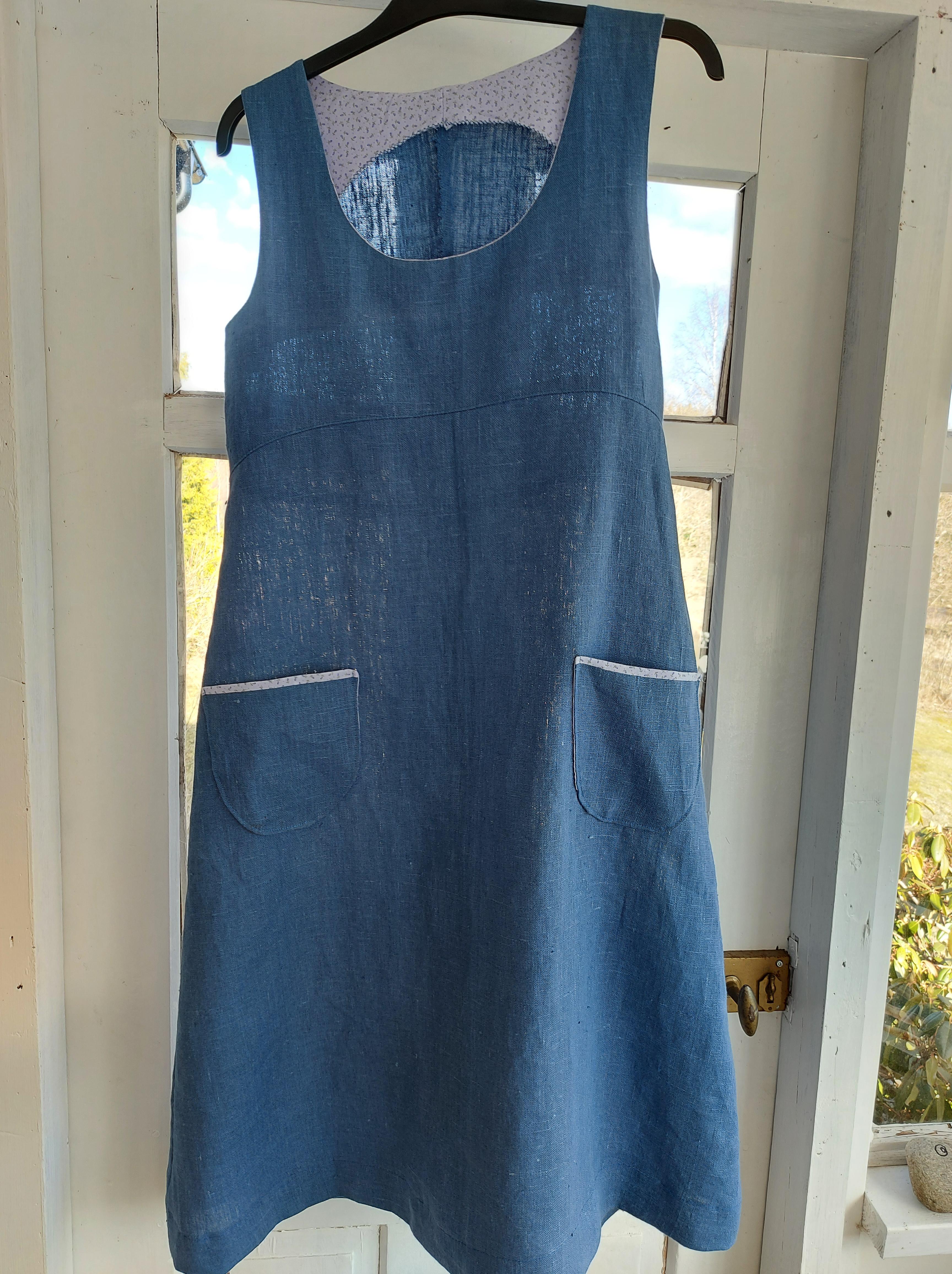 Blå linne klänningen utan ärmar, med påsydda fickor som har en liten kant av blommigt tyg