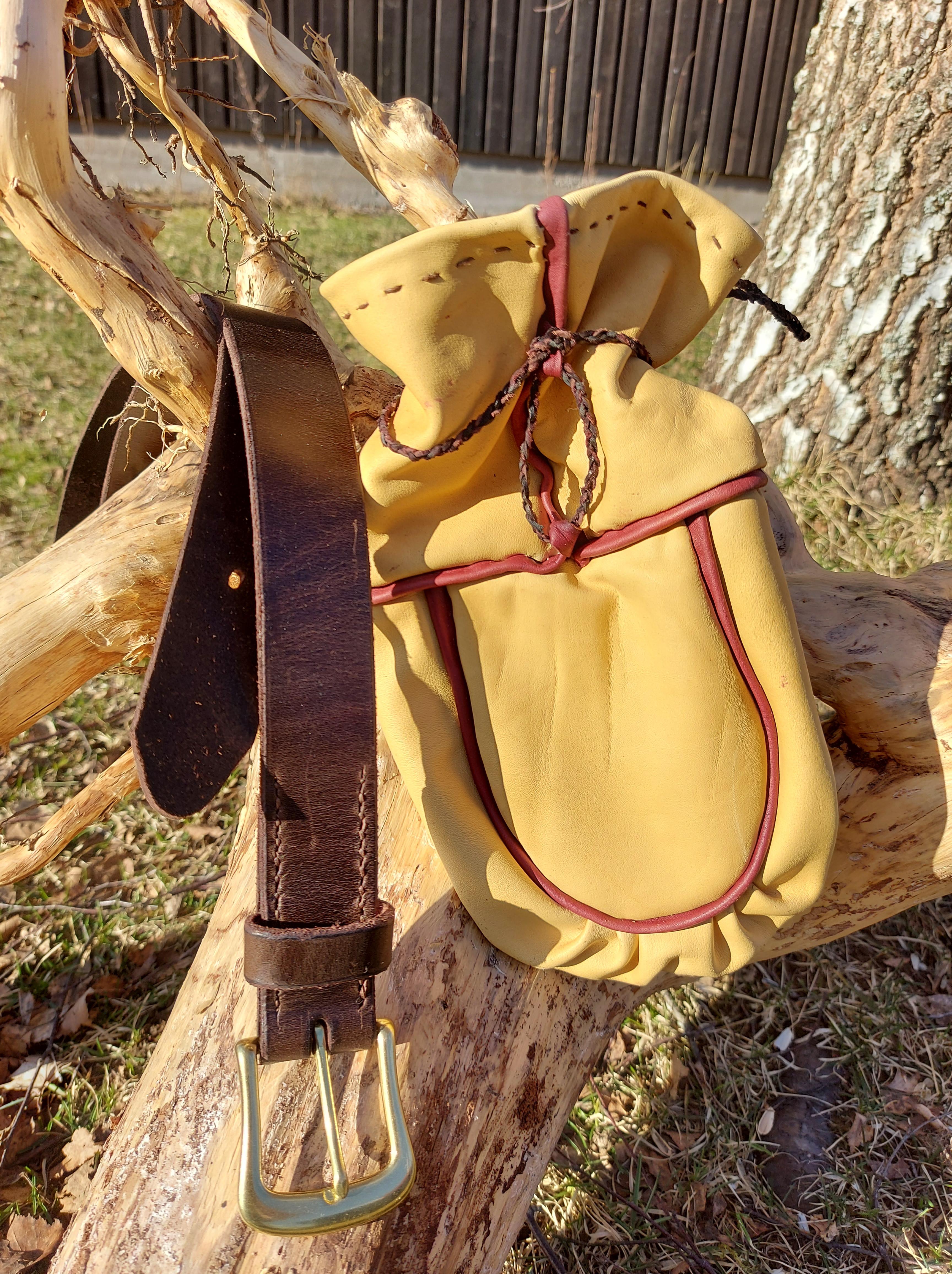 Brunt läderbälte med mässing spänne ,liten väska/påse i gult skinn med rödbruna kanter