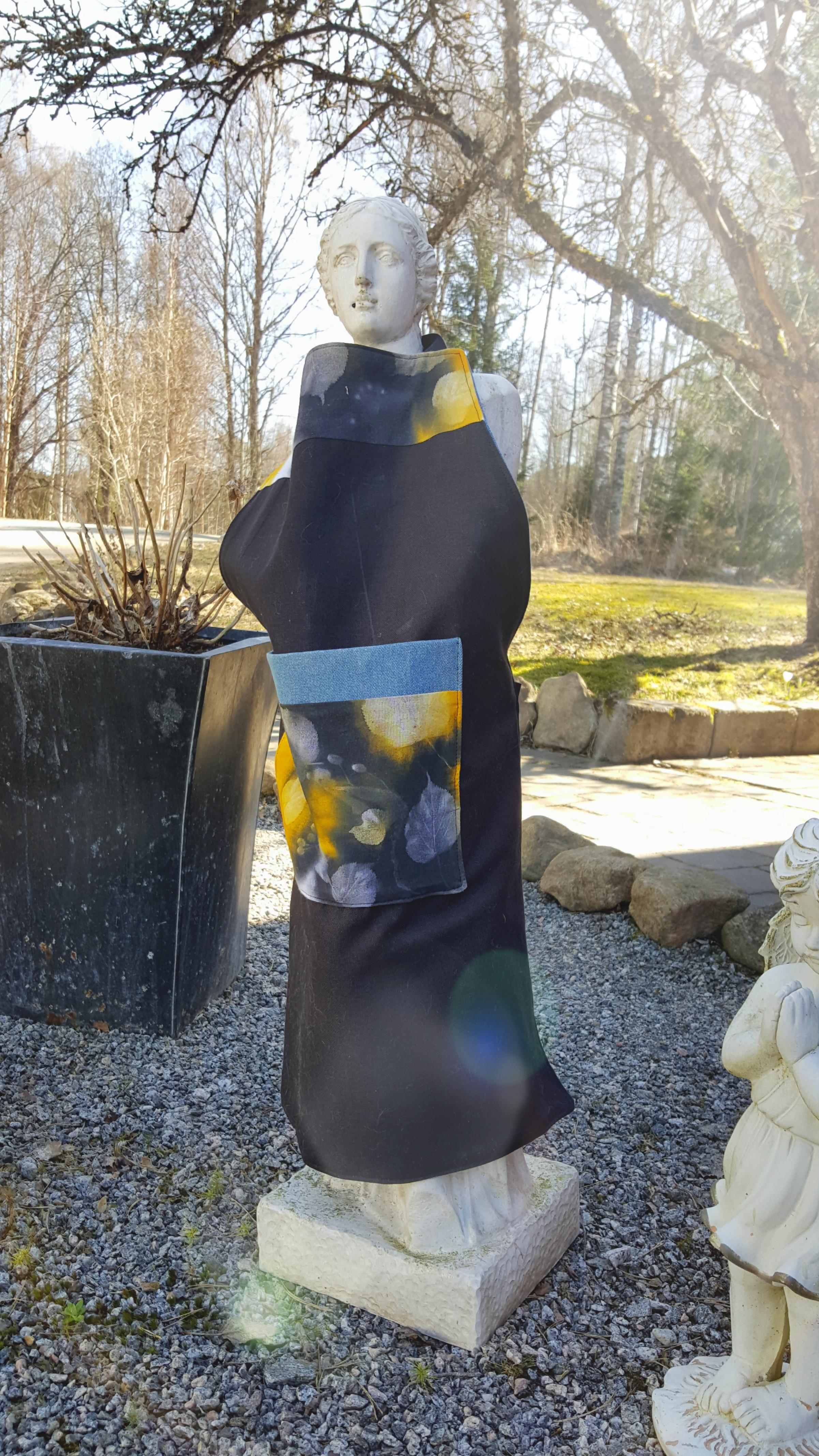 Förkläde gjort i svarttyg med en ficka i gult och svart soltryck