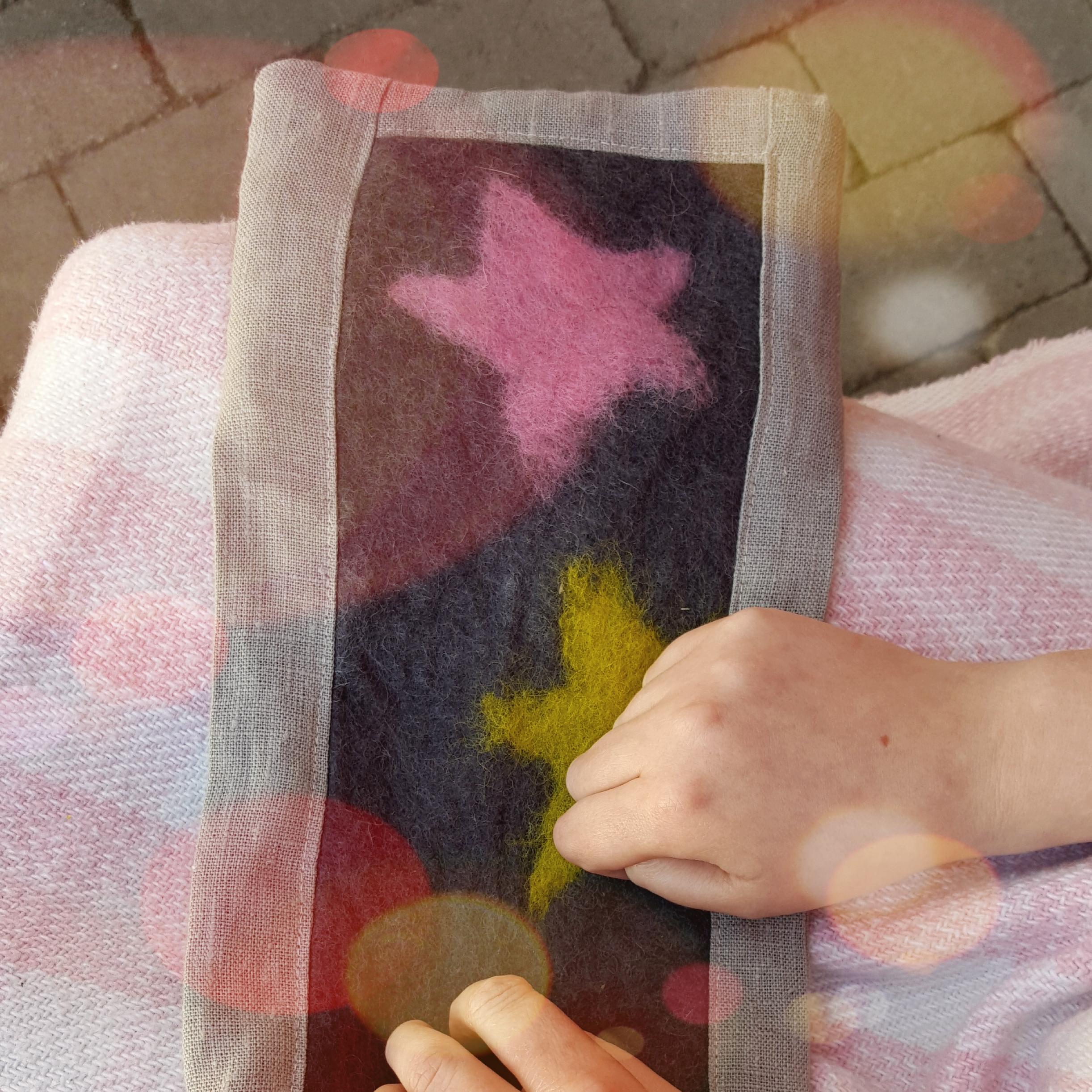 Tovad grytlapp med stjärnor i gult och rosa på mörkbotten. Grytlappen har en kant i oblekt linnetyg.