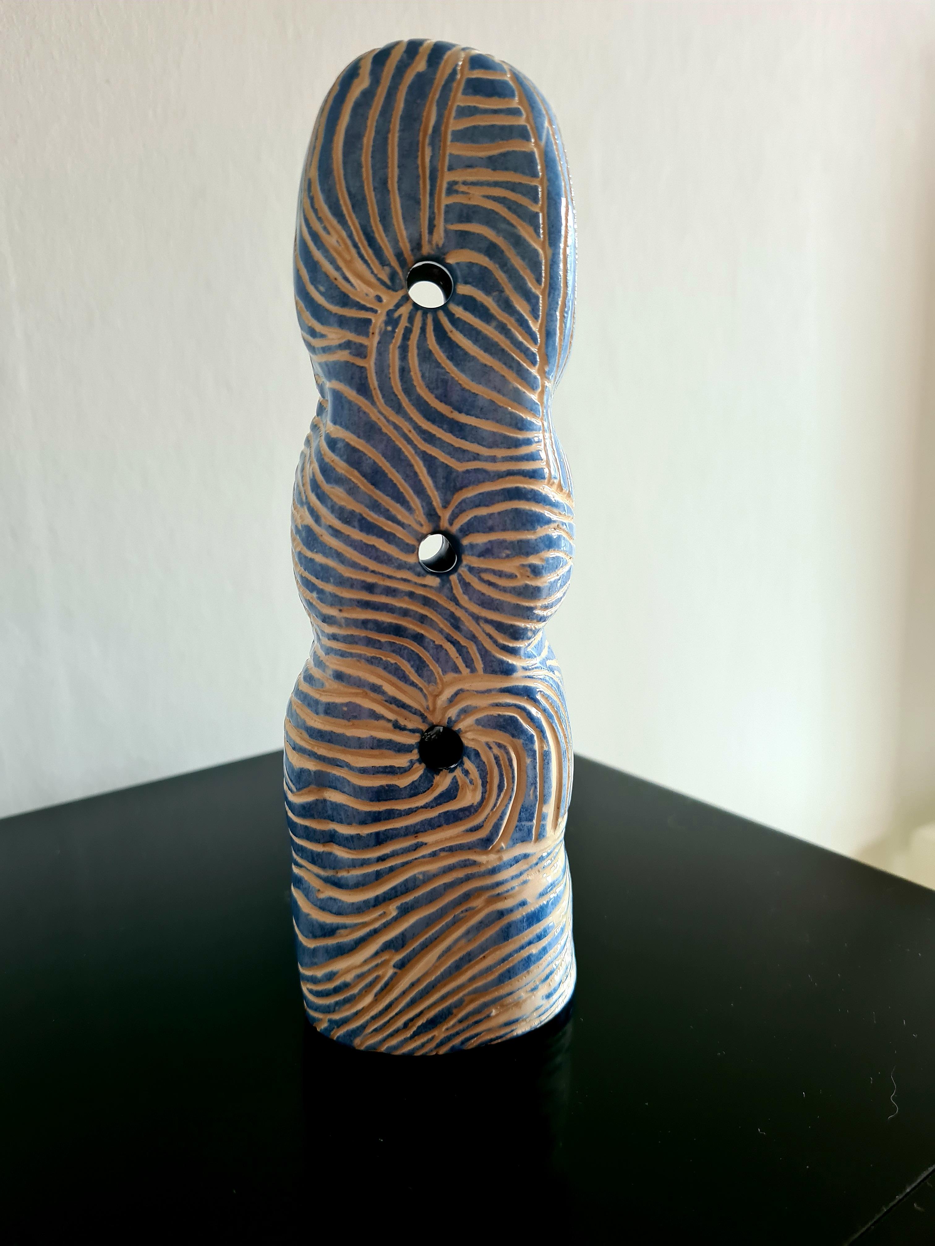 Avlång keramikskulptur med mjuka former och tre genomskärningar med ristad yta