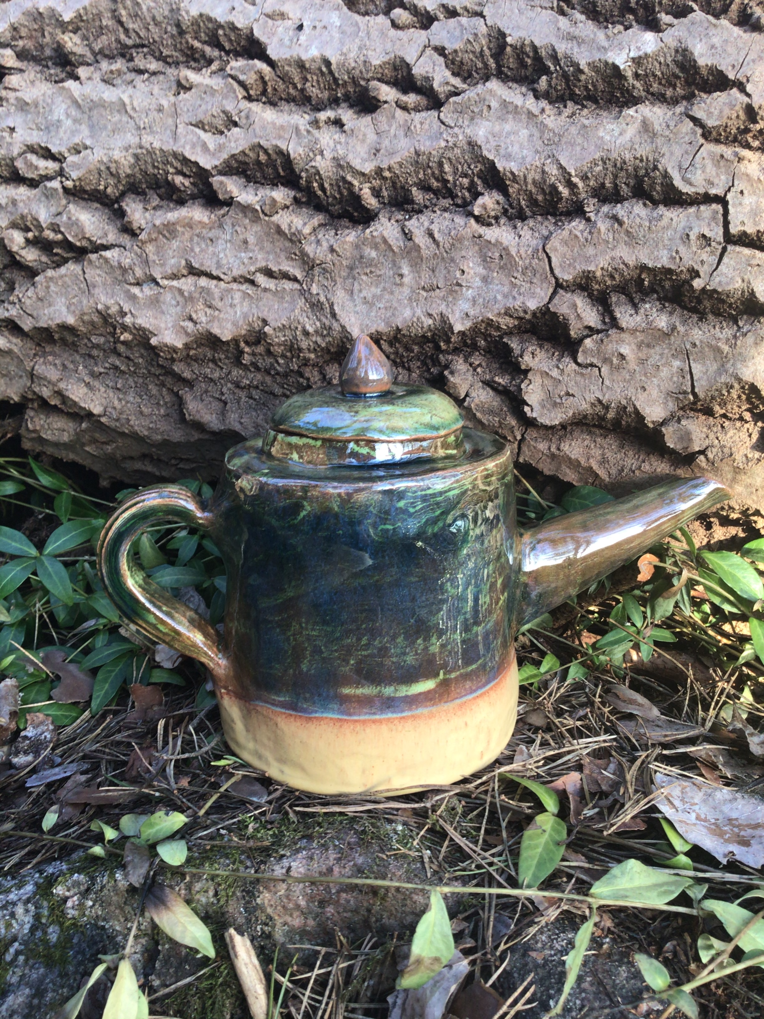 Tekanna i keramik med blågrönglasyr upptill och botten är oglaserad