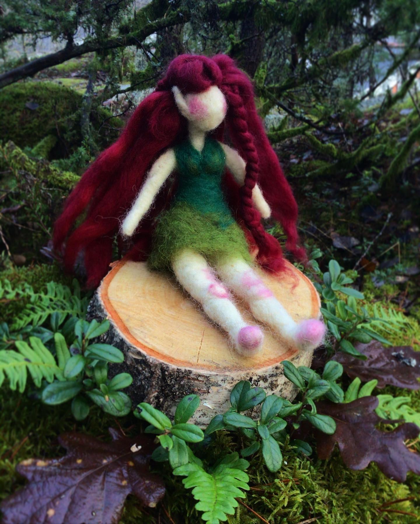 Tovad älva med grön kjol och lilarött hår . Älvan sitter på en stubbe