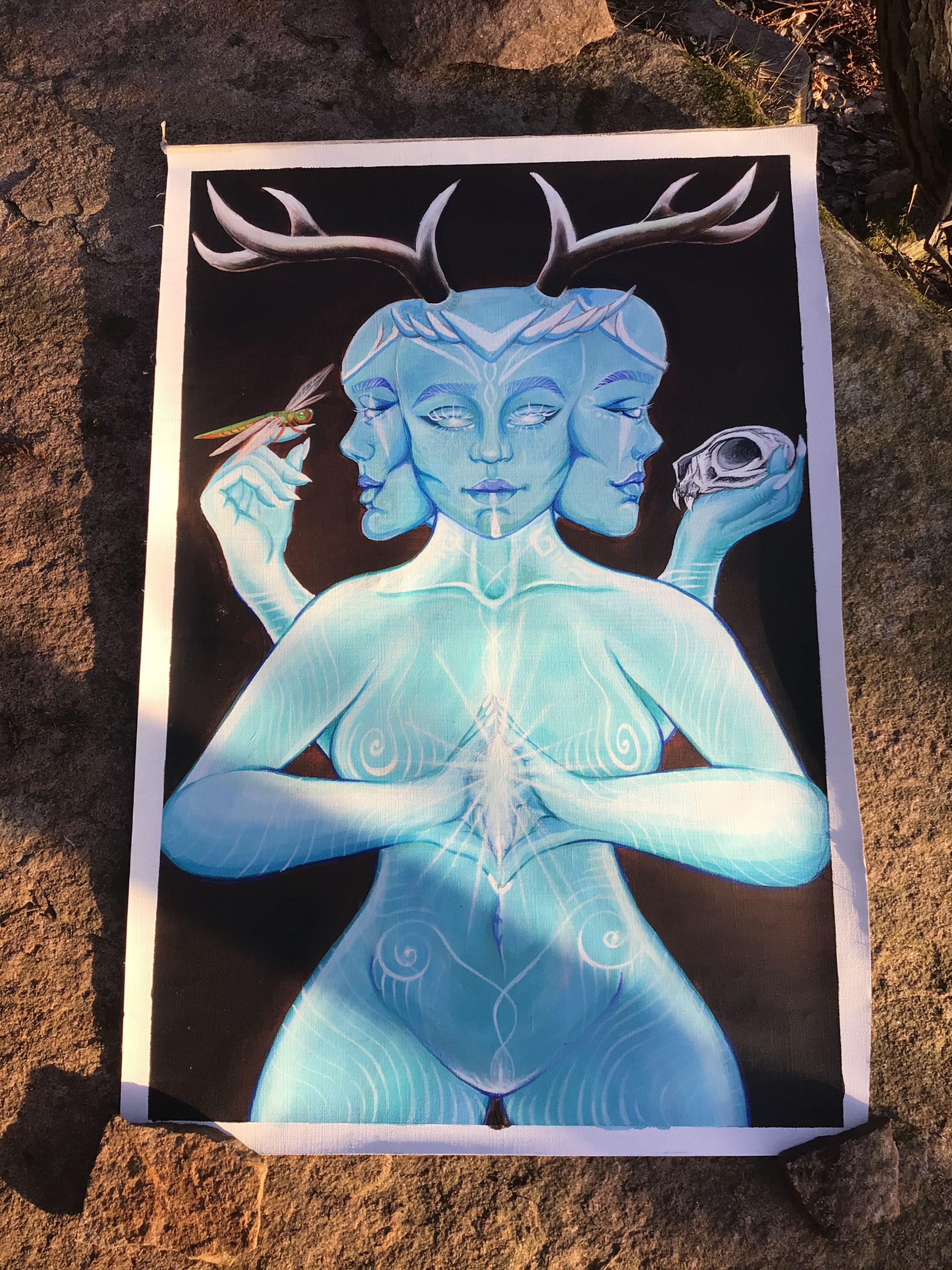 Målning av en kvinna med tre ansikten. Kvinnan är blå och har djur horn och i sina händer håller hon en en sten som lyser, ett djurkranium och en trollslända