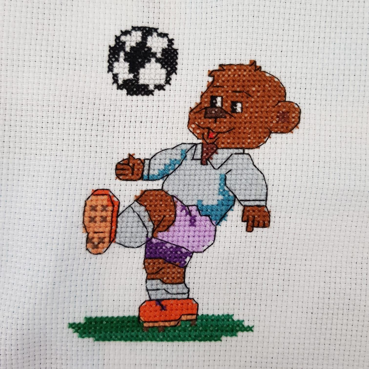 Korsstygns broderi. Motivet är en björn som spelar fotboll.