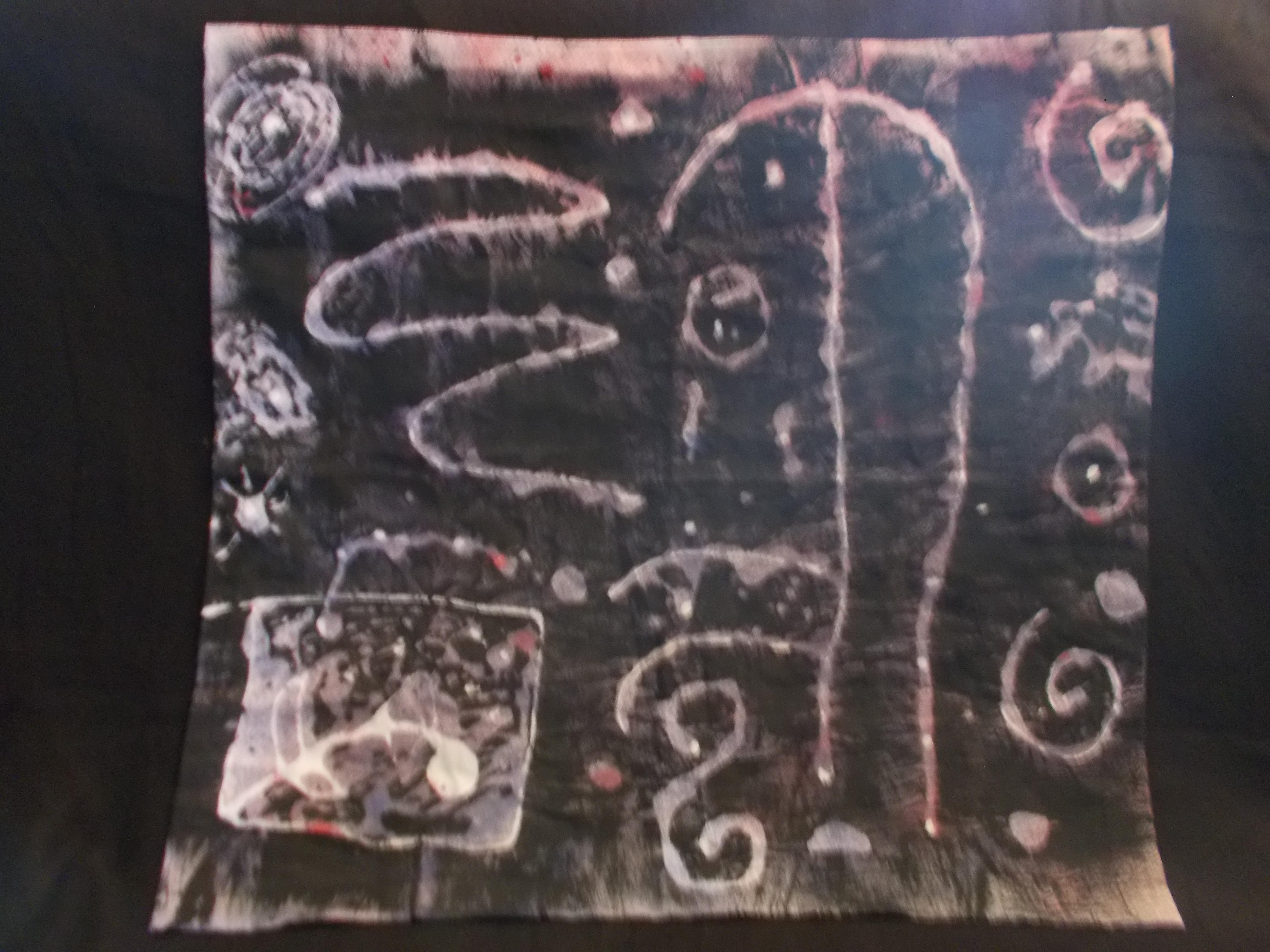 Tyg som mönstrats med mjölbatik i svart och lila färger med vitt mönster i olika former