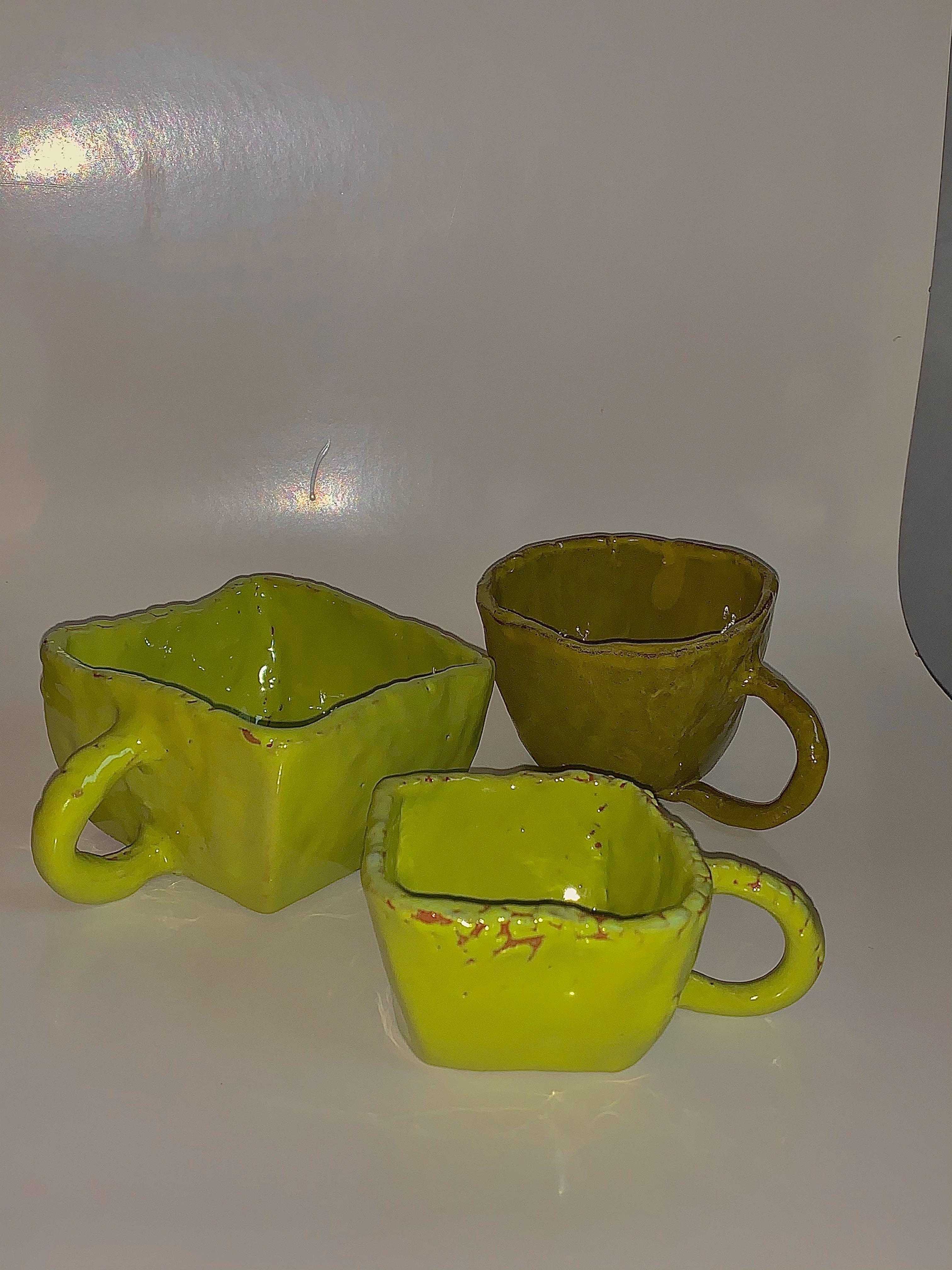 Tre koppar i olika storlekar: Kopp 1 & 2 terracotta lera med en grön glasyr. Kopp 3 med brun lera samt gul glasyr