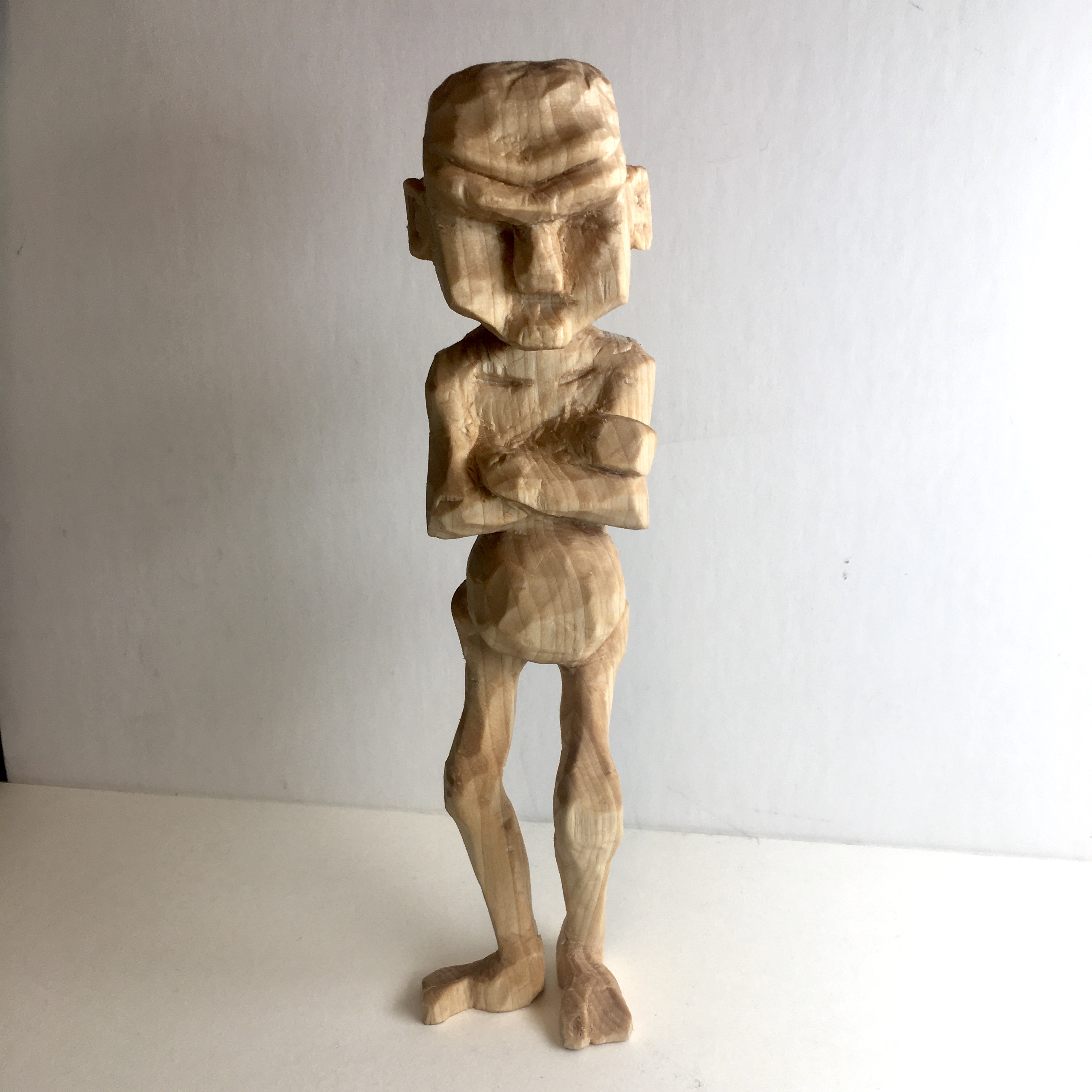 En täljd gubbe som står med armarna i kors.