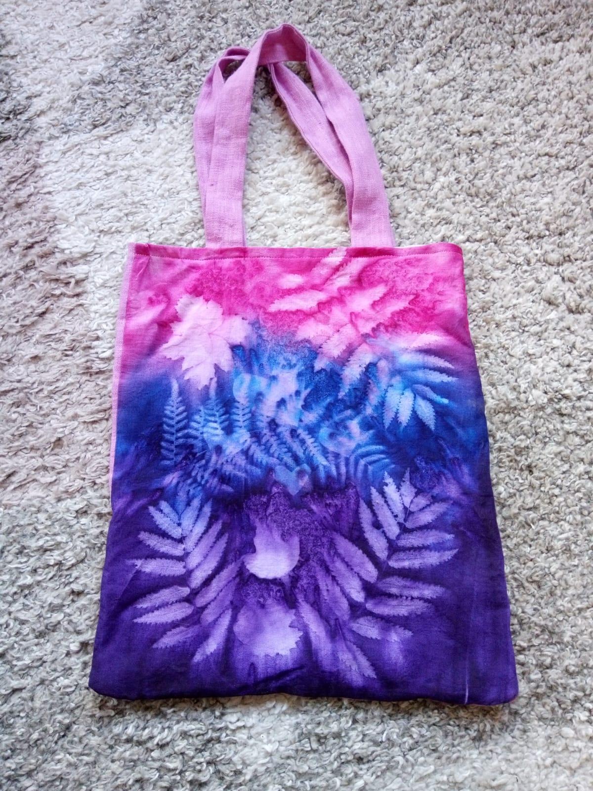 Väska med soltryck i rosa och lila färger med mönster av olika blad och löv