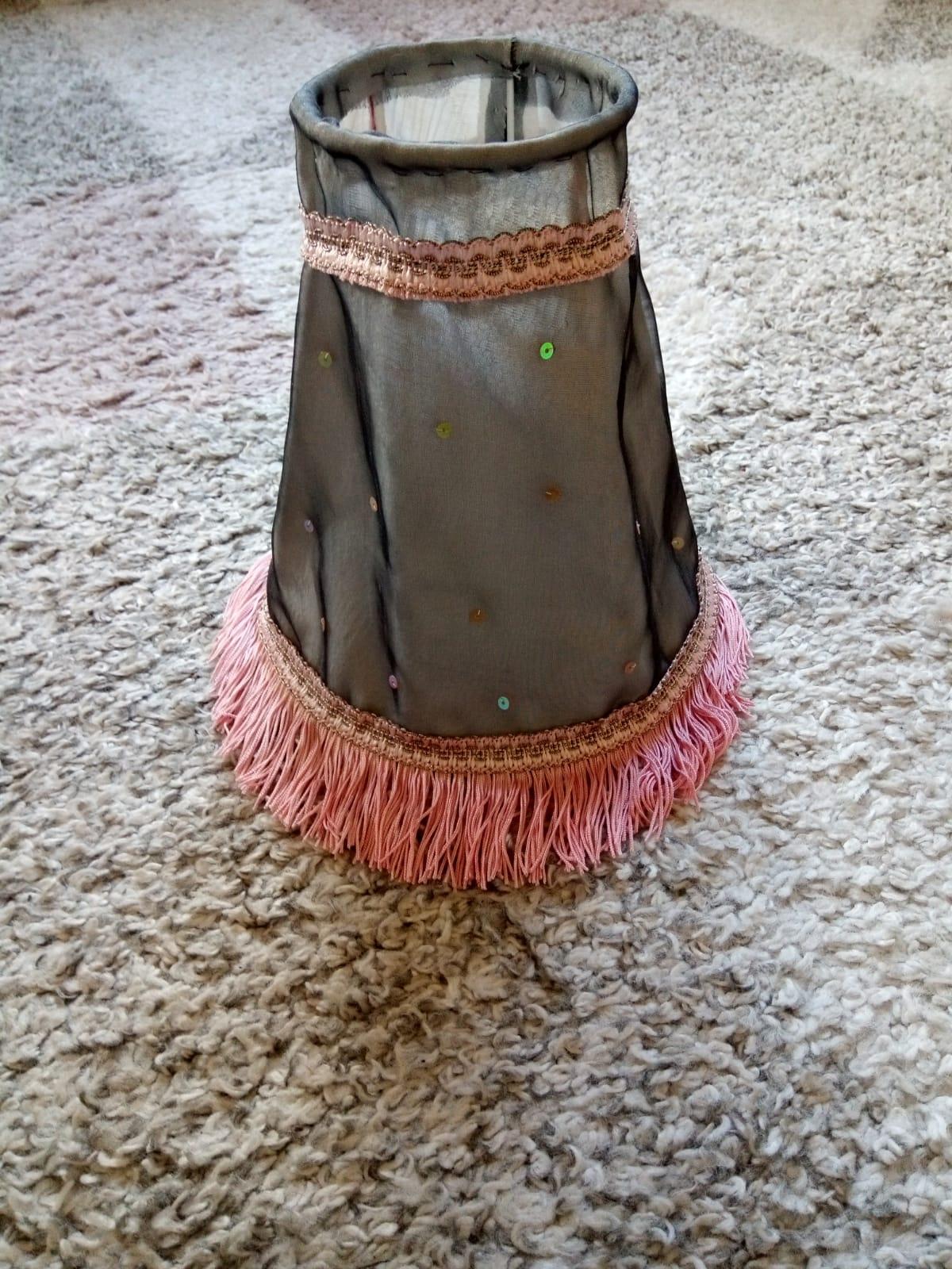 En lampskärm i re:design. Grått genomskinligt tyg med paljetter och en franskant längst ner