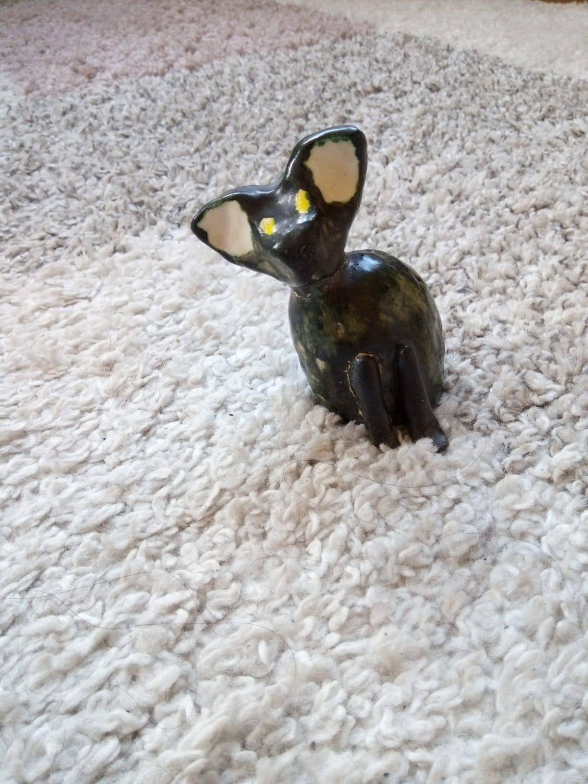 En katt i keramik med svart glasyr och gula ögon