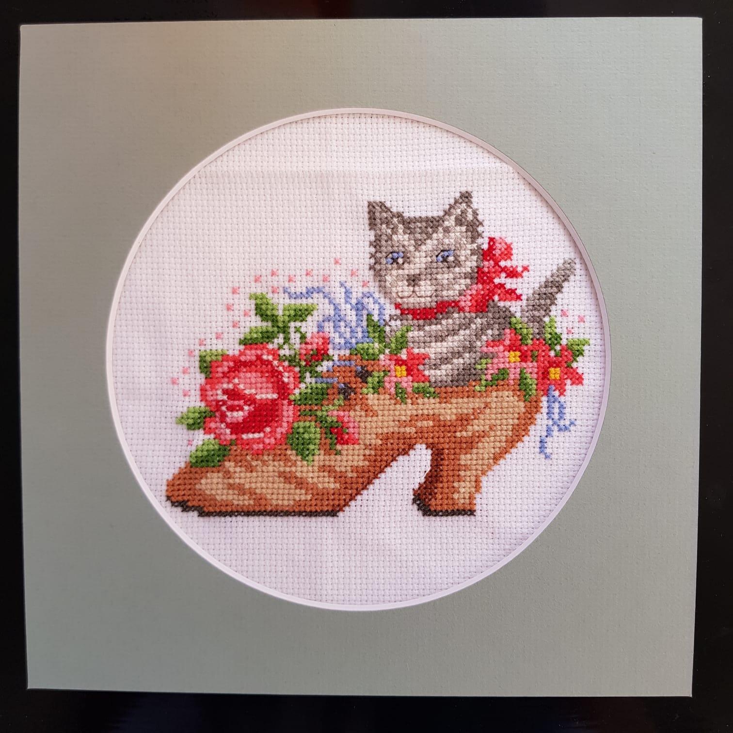 Korsstygnsbroderi. Motivet är en randig katt som sitter i en sko med blommor i.