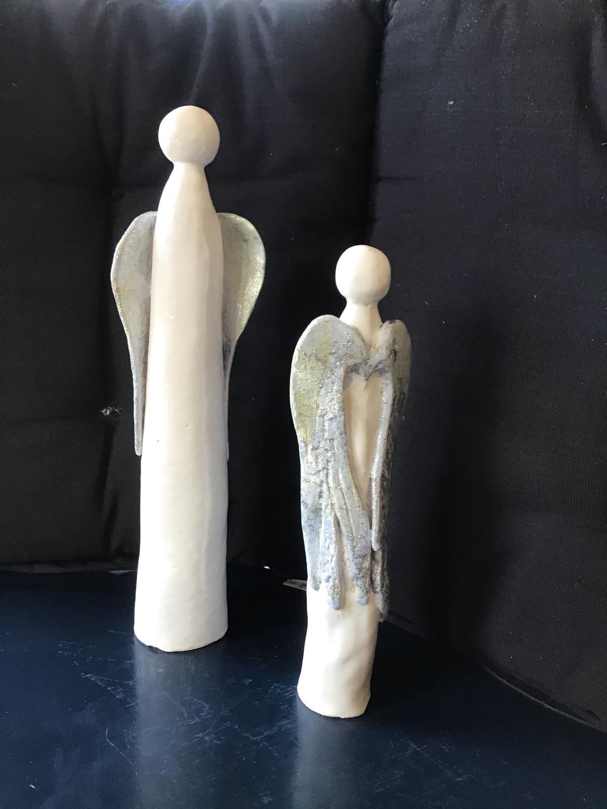 Två långsmala änglar i vitkeramik med grå vingar