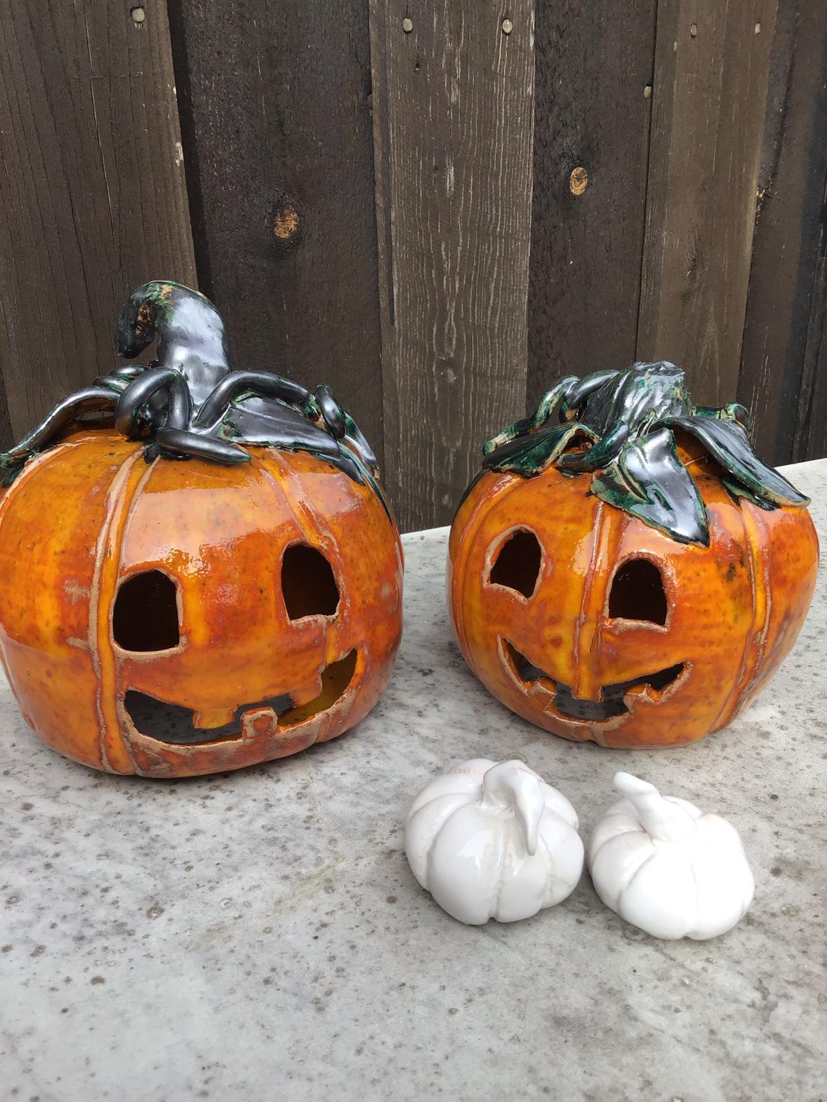 Två stycken pumpor i keramik glaserade i orangeglasyr och med stjälk och blad i grönsvart glasyr. Framför står två små vitlökar i keramik med vit glasyr