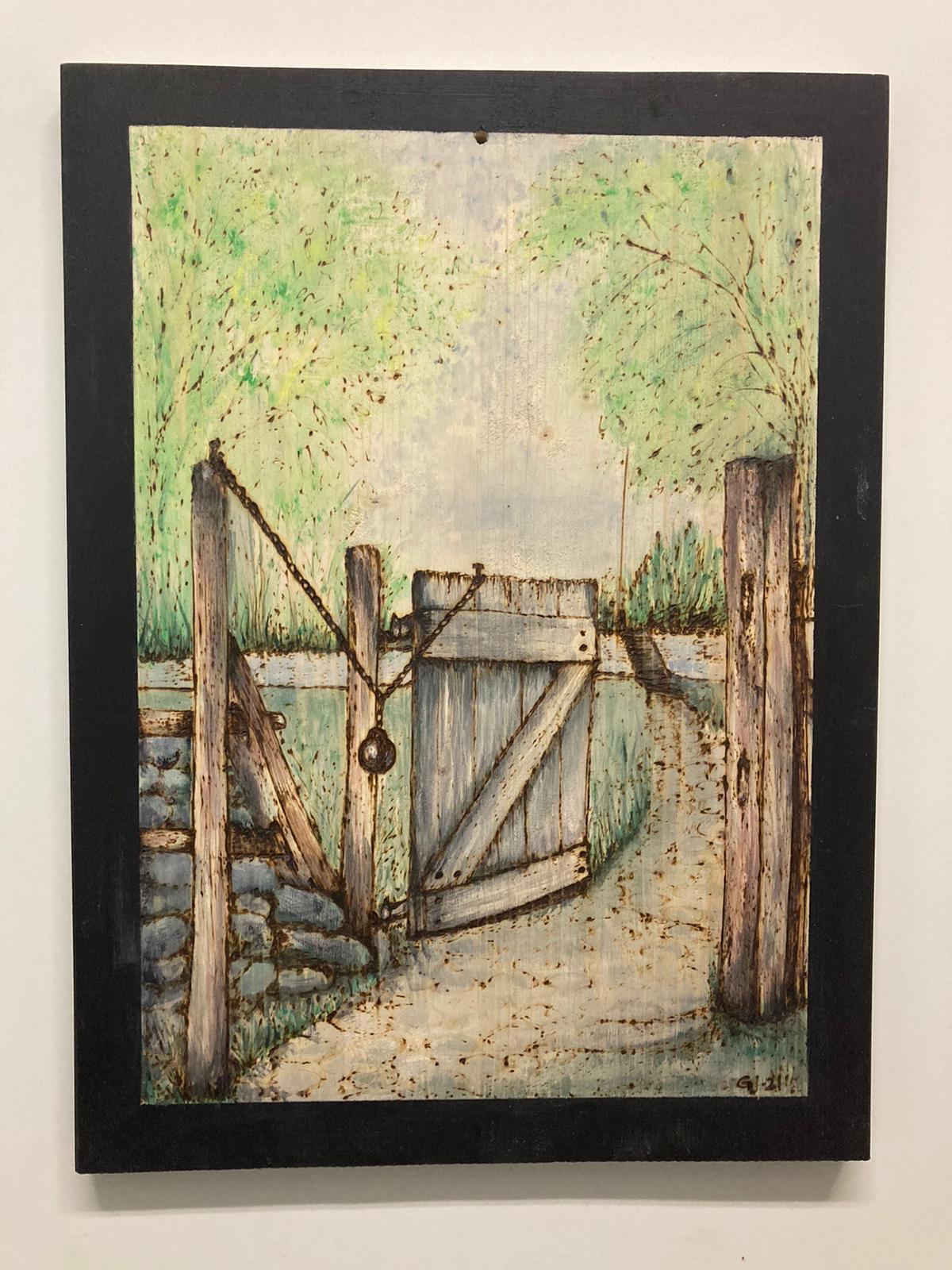 Trätavla med en grind som öppnar sig mot en stig i naturen. Motiv bränt ned brännarna och målade med akryl.