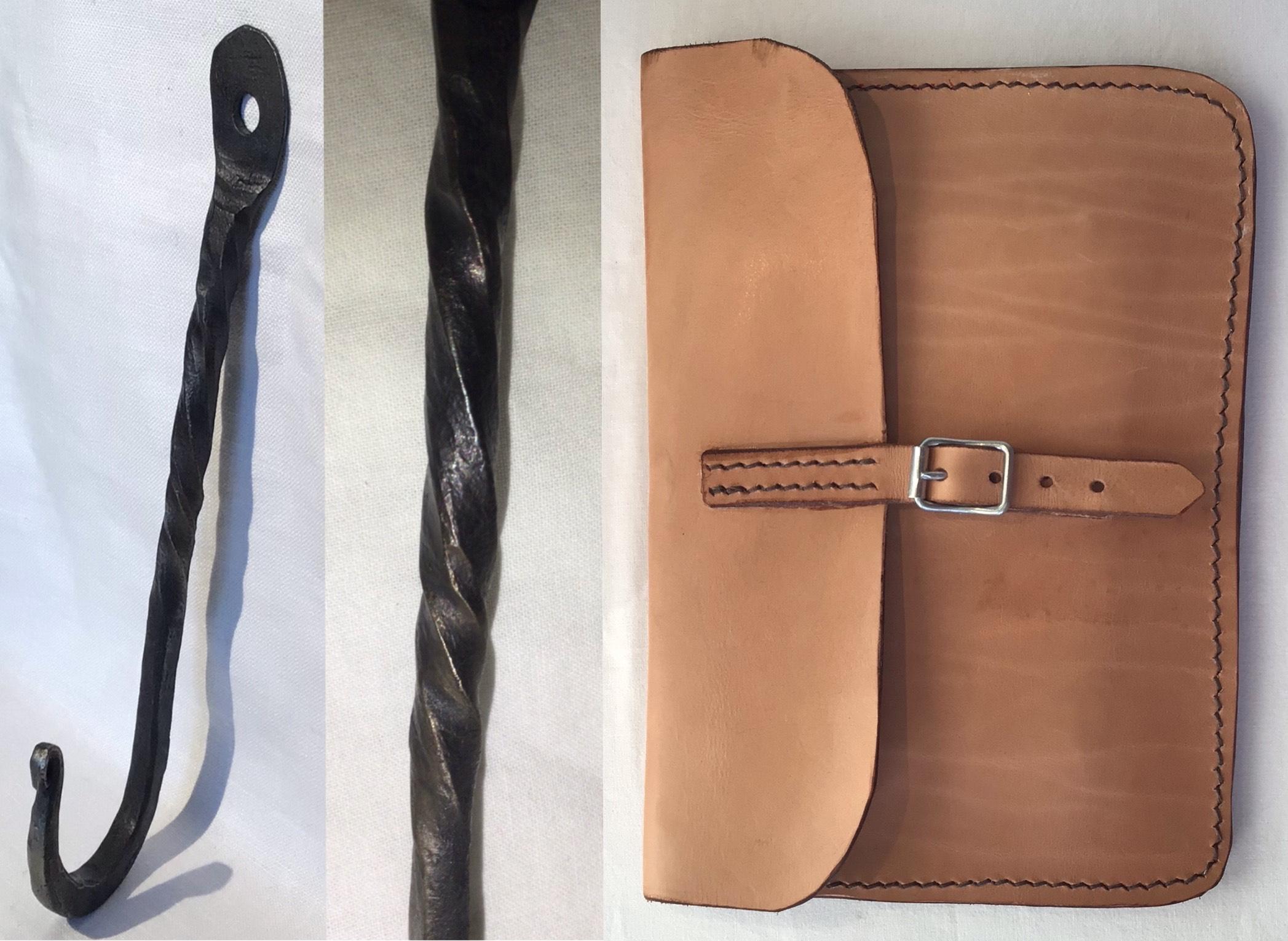 En smidd, vriden och lång järnkrok. En handsydd kuvertväska i ljust läder med spänne.