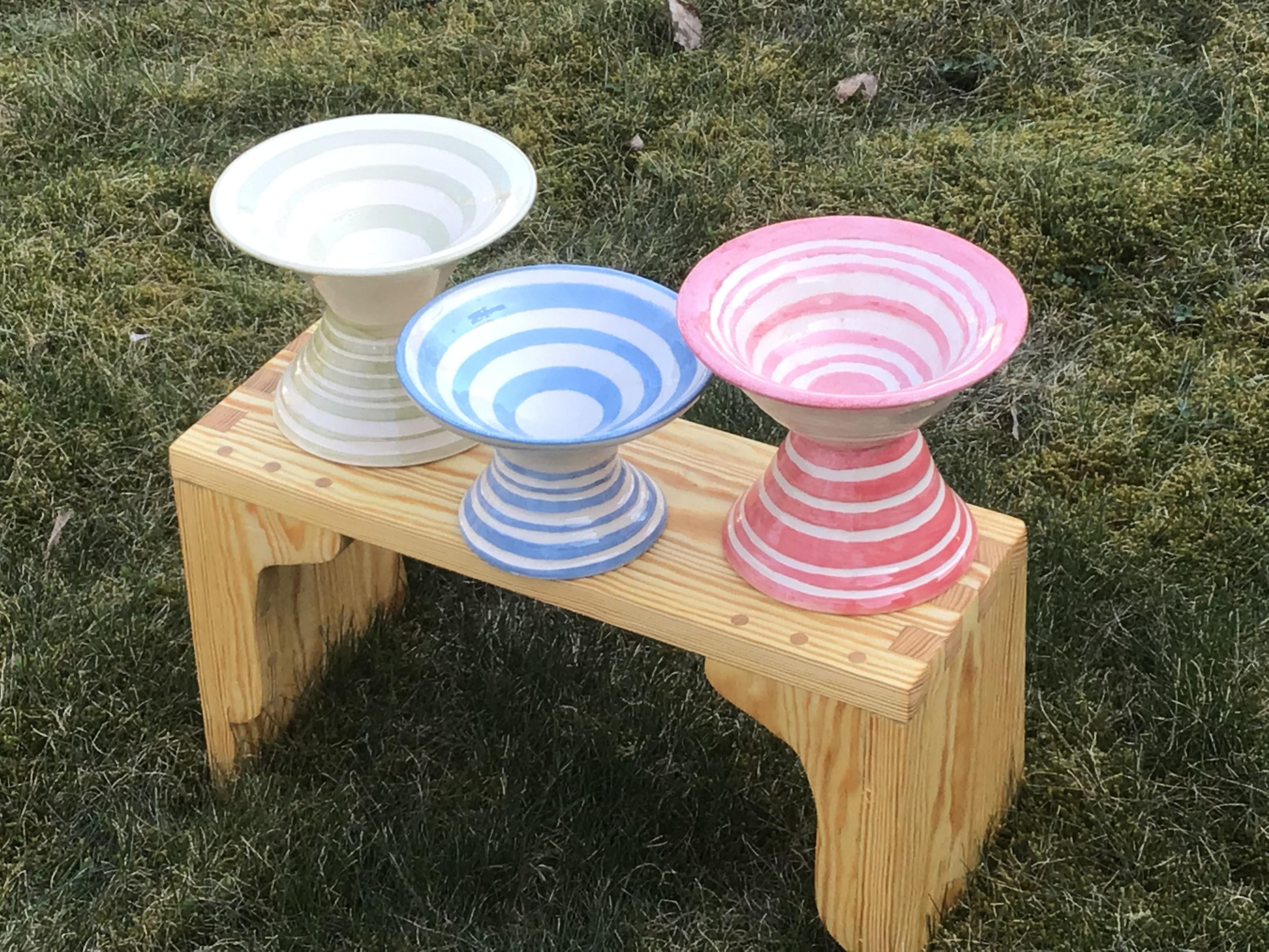 Tre drejade keramikskålar på fot, med horisontella linjer i grönt, blått och rosa.