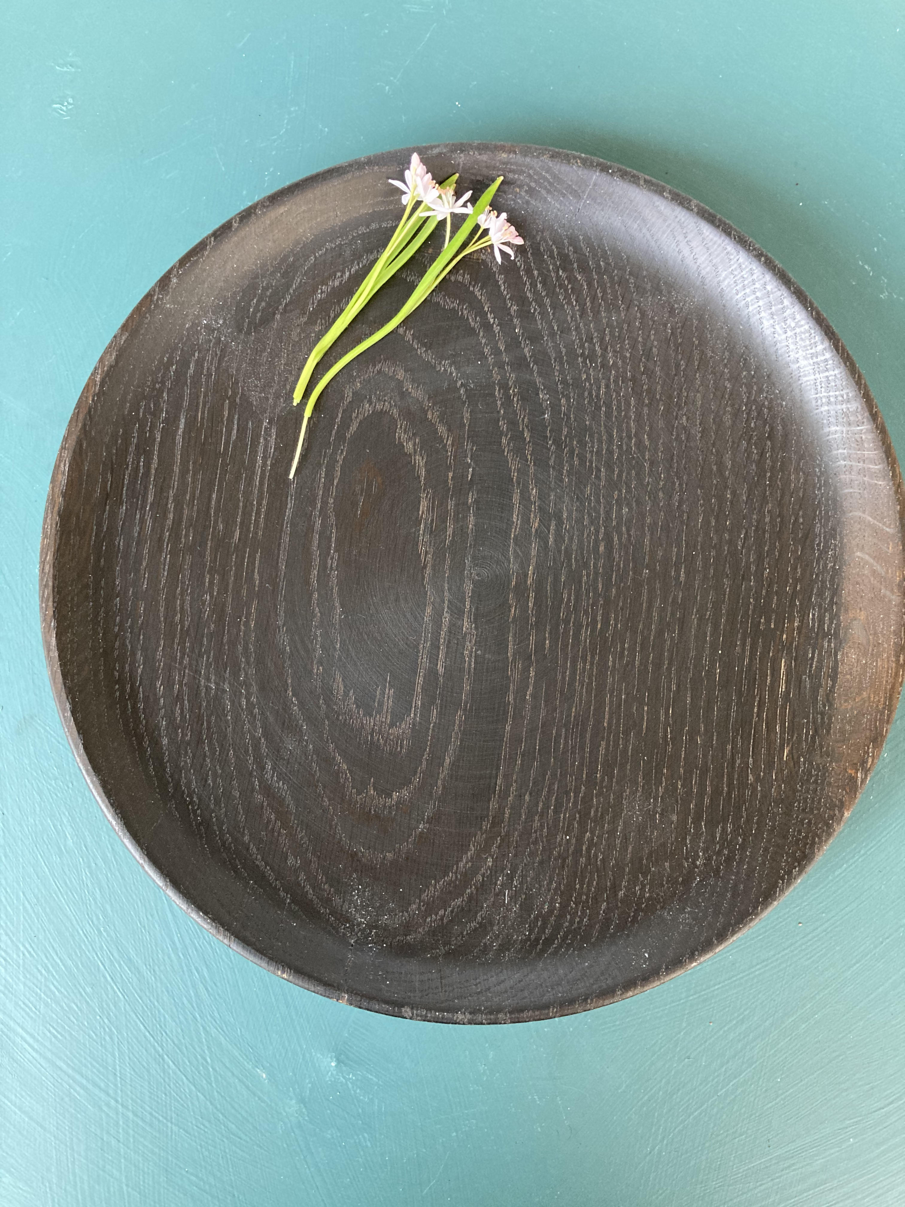 Ett svarvat fat i ek med tydlig ådring, 27 centimeter i diameter. Det är ganska mörkt i färgen eftersom det är svartbetsat, det vill säga bestruket med en vätska som reagerar med garvsyran i ek. Man blandar vatten och ättika in glasburk och lägger i järn, i det här fallet rostiga spikar, som får ligga en tid tills det bildas ett oljigt lager på ytan. Då är det färdigt att strykas på träet med en pensel. Ju fler gånger man stryker, desto mörkare blir ytan. Ett brunt fat står på en turkos yta. På fatet ligger några små rosa blommor.