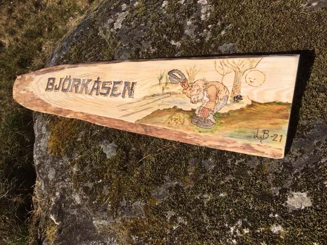Graverad träskylt gjort med brännpenna och målad med akrylfärger. Motivet är ett troll som hälsar och har texten Björkåsen
