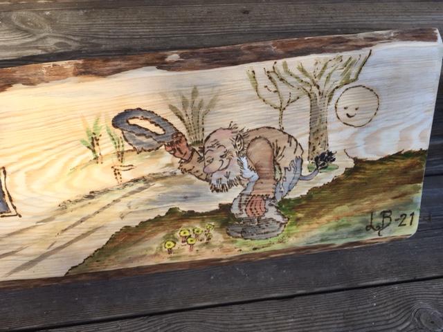 Närbild av träskylt gjort med brännpenna. Motivet är ett troll som hälsar och har texten Björkåsen