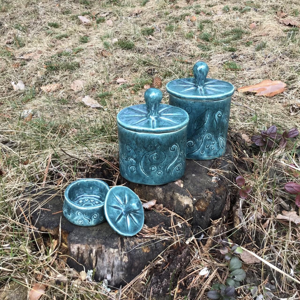 Tre keramikburkar i olika storlekar med lock. Ristat mönster med spiraler och blad samt en glasyr i blågrön nyans.