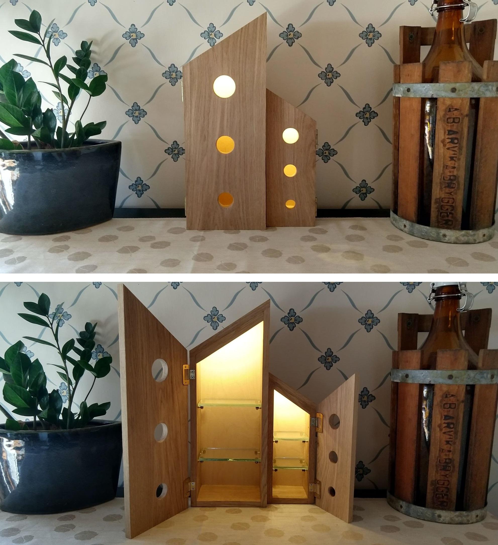 Skåp:Trädskåp i ek bestående av två delar med snedtak. Den ena delen är en kopia av den första med mindre i formatet och är spegelvänd. I luckorna på skåpet finns tre runda hål som går vertikalt och blir mindre och mindre desto längre ned deras placering är. Ur hålen strömmar ett varmt ljus. Inuti skåpen finns en dold ledslinga i taket som lyser upp insidan. Skåpen har två hyllplan av glas.