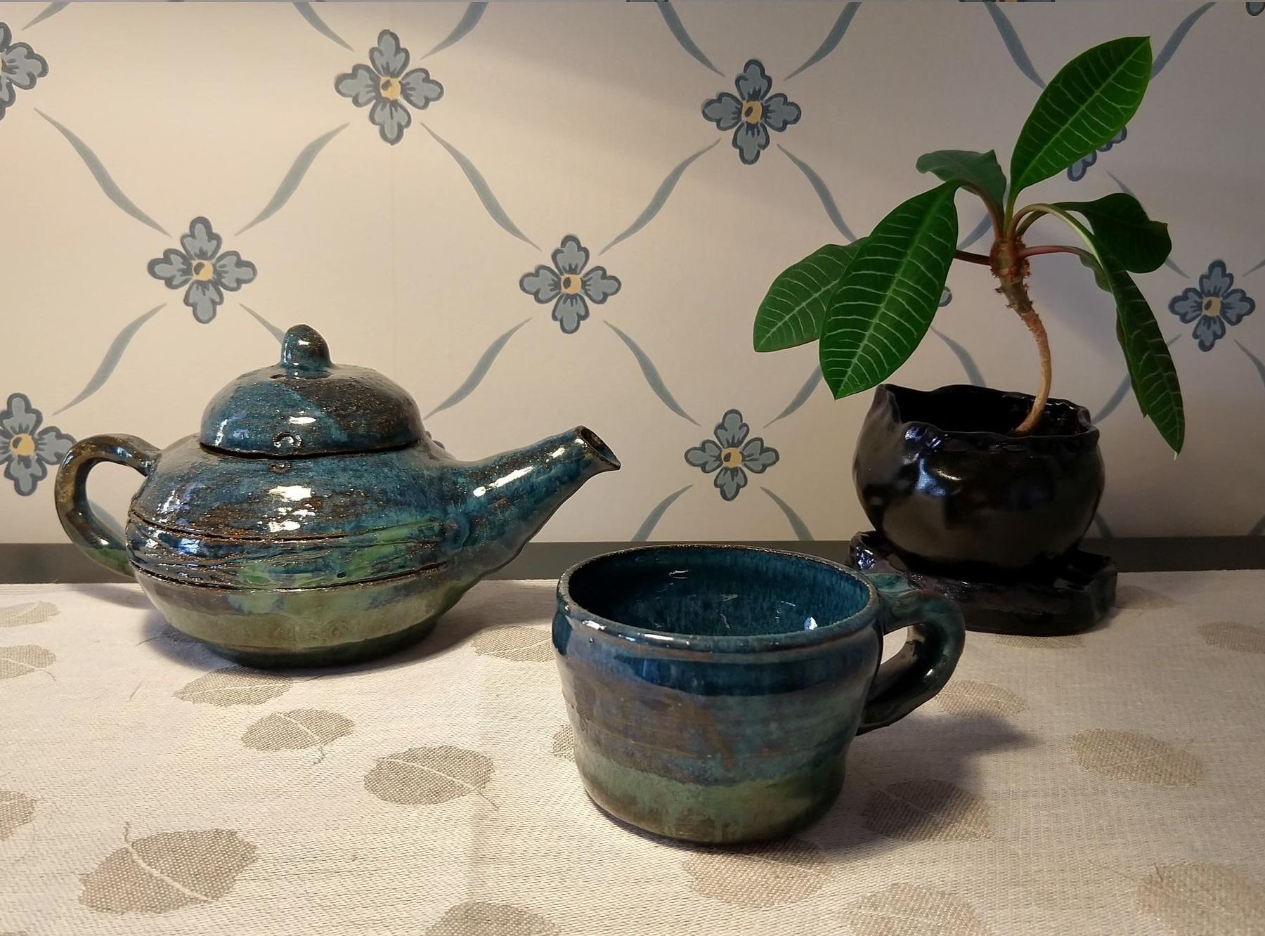 Tekanna, mugg och kruka:En drejad tekanna och mugg i blåa och gröna färger, intill dessa står en handgjord liten keramikkruka i svart.